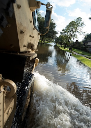 A military vehicle drives through water in a flooded street.