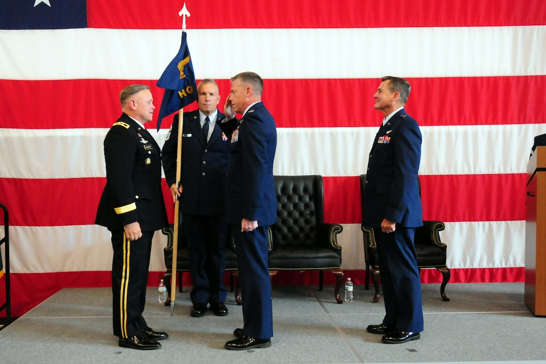 Col. Jeremy Horn, incoming commander of the Washington Air National Guard, salutes Maj. Gen. Bret Daugherty, Adjutant General of the Washington National Guard as outgoing commander Brig. Gen. John Tuohy looks on at right and Washington Air National Guard Command Chief Master Sgt. Max Tidwell holds the guidon.