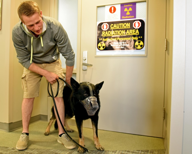 Senior Airman Steven Albion, 92nd Security Forces Squadron military working dog handler, and MWD Rosso pose for a photo after x-ray exam Aug. 22, 2017, at Fairchild Air Force Base, Wash. X-ray exams are administered to the dogs anytime a health concern is presented or as the dogs approach a senior age.