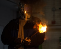 U.S. Air Force Airman 1st Class Jordan Mann, 1st Maintenance Squadron metals technology journeyman, lights a blow torch at the metals technology shop at Joint Base Langley-Eustis, Va., Aug. 17, 2017. The metal technicians use blow torches to melt and break down a piece of metal from equipment such as cargo crates. (U.S. Air Force photo by Senior Airman Derek Seifert)