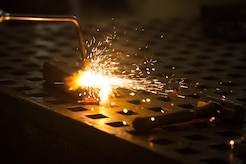 A blow torch burns a piece of metal at the metals technology shop at Joint Base Langley-Eustis, Va., Aug. 17, 2017. The 1st Maintenance Squadron metals technology shop supports the flightline and other units on JBLE that require specialized metal work. (U.S. Air Force photo by Senior Airman Derek Seifert)