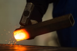 A U.S. Air Force Airman strikes a burning piece of metal with a hammer to break it down at the metals technology shop at Joint Base Langley-Eustis, Va., Aug. 17, 2017. The main job of 1st Maintenance Squadron metal technology shop is to repair bushings, remove bolts and manufacture tools for crew chiefs and other shops across the installation. (U.S. Air Force photo by Senior Airman Derek Seifert)