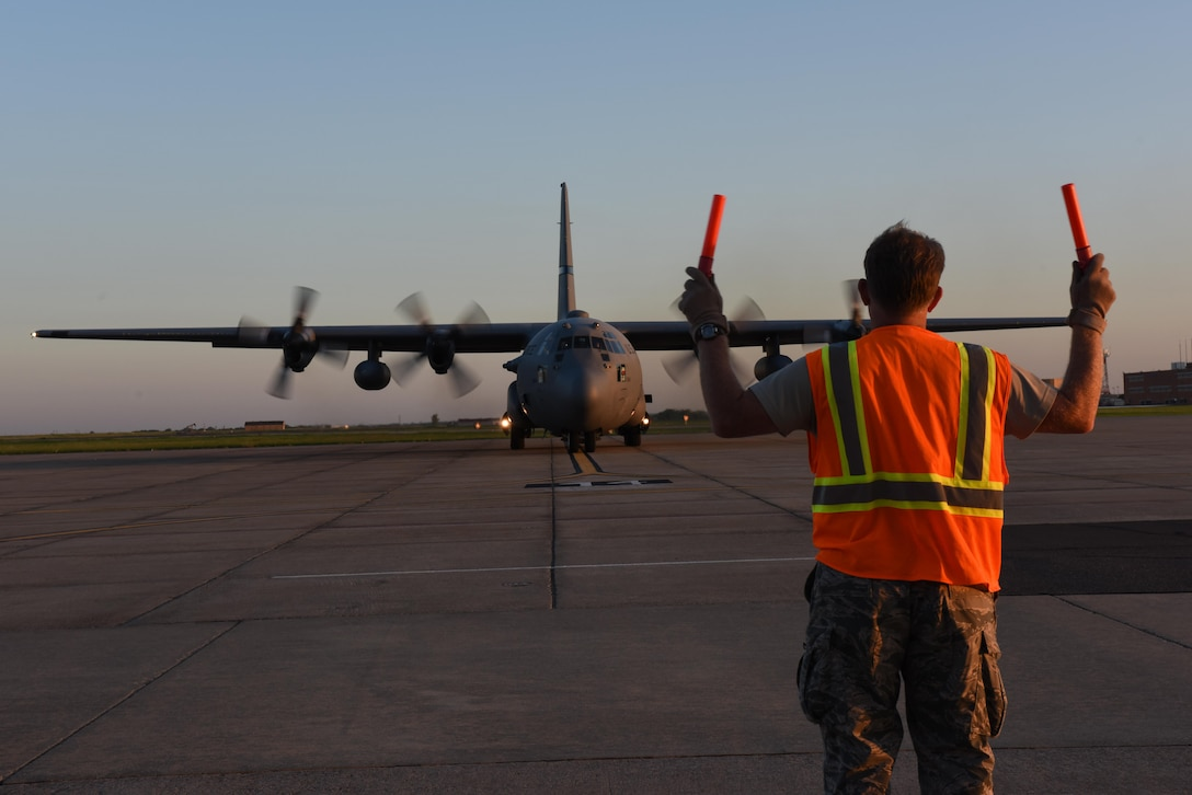 An airfield manager from the 137th Special Operations Wing, Will Rogers Air National Guard Base in Oklahoma City, marshals a C-130 Hercules from the 136th Airlift Wing, Naval Air Station Fort Worth Joint Reserve Base at Carswell Field, Texas, as it takes off from Will Rogers Air National Guard Base, Aug. 28, 2017. The 137th Special Operations Wing deployed about 40 medical and aeromedical evacuation Airmen and equipment in support of the Texas Military Department and their relief efforts following Hurricane Harvey. (U.S. Air National Guard photo by Staff Sgt. Kasey Phipps/Released)