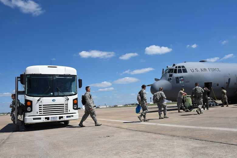 Airmen from the 137th Special Operations Medical Group, Will Rogers Air National Guard Base, Oklahoma City, exit a bus and board a C-130 Hercules from the 136th Airlift Wing, Naval Air Station Fort Worth Joint Reserve Base at Carswell Field, Texas, Aug. 29, 2017, at Will Rogers Air National Guard Base. The Airmen are part of the 137th Special Operation Wing's deployment of nearly 40 medical and aeromedical evacuation Airmen and equipment in support of the Texas Military Department and their relief efforts following Hurricane Harvey. (U.S. Air National Guard photo by Staff Sgt. Kasey Phipps/Released)