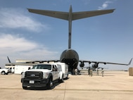 A truck and trailer are backed into a C-17 aircraft