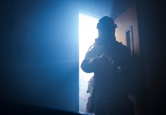 A firefighter enters a room during a training exercise of a building fire at Cannon Air Force Base, N.M., Aug. 29, 2017. Firefighters train on this scenario once per year, searching through buildings filled with smoke, serving as an example of the many training events they complete to maintain mission readiness at all times. (U.S. Air Force photo by Senior Airman Lane T. Plummer)