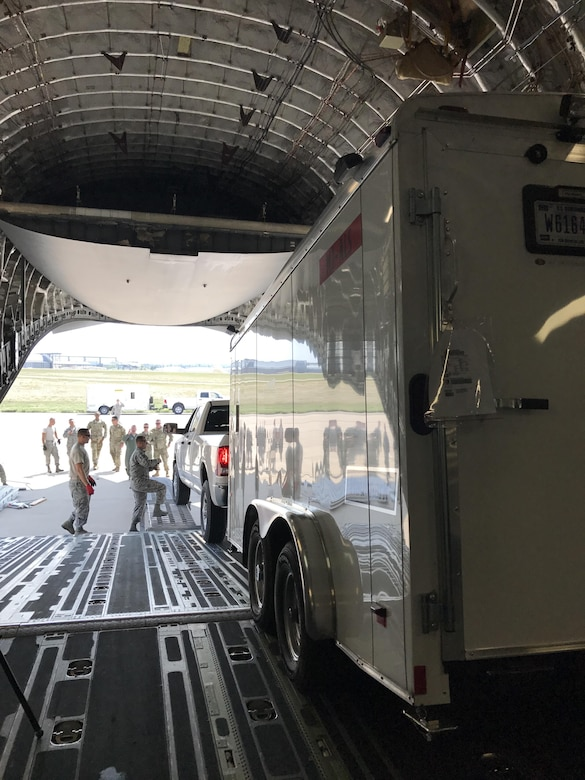 two trucks and trailers driving onto a C-17 aircraft