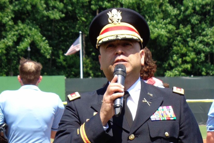 a soldier stands with a microphone and sings.