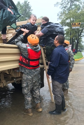 Members of the Texas National Guard's 386th Engineer Battalion and a local volunteer help children from a military vehicle in Cypress Creek, Texas, Aug. 29, 2017. Texas Army National Guard photo by Capt. Martha Nigrelle