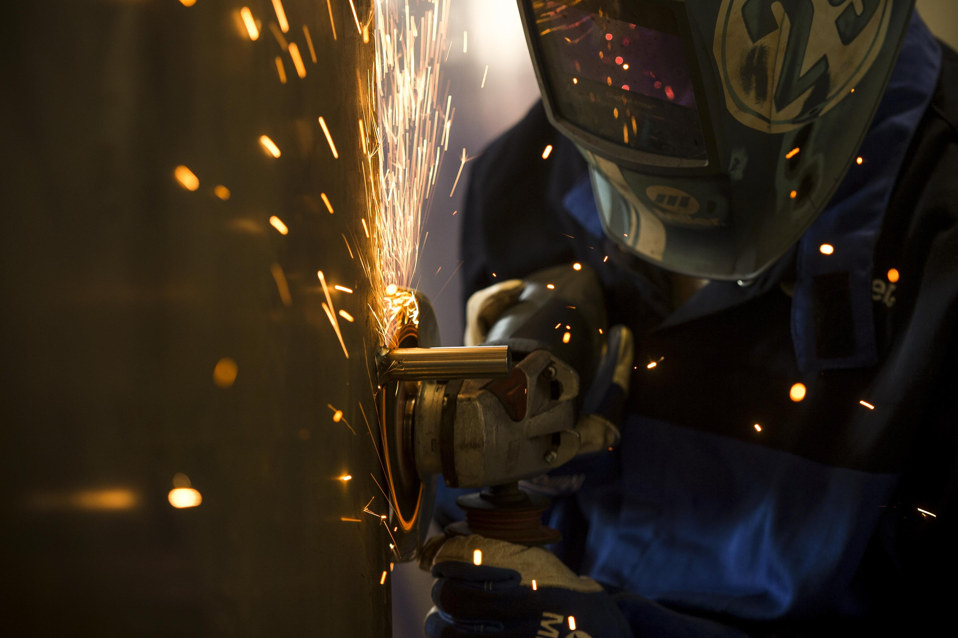 An Air Force airman removes a piece of metal at the metals technology shop.