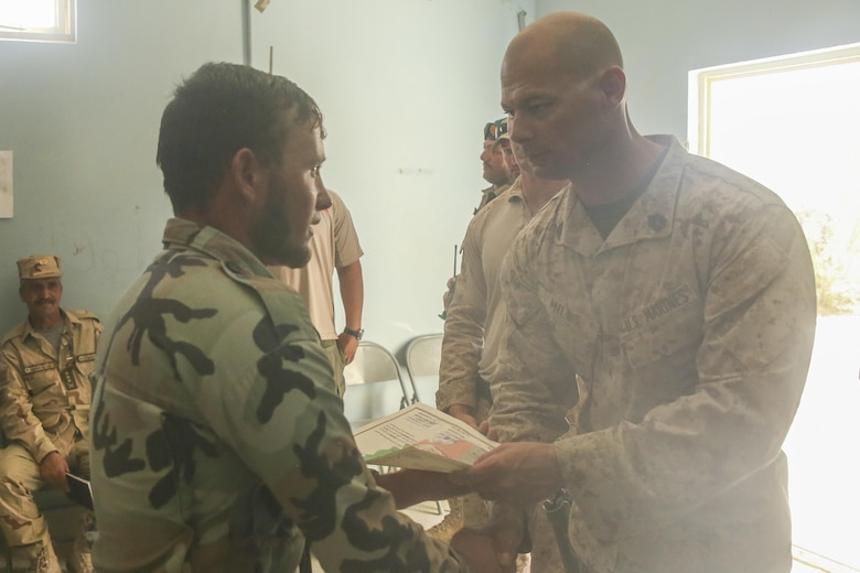 A U.S. Marine advisor with Task Force Southwest hands a certificate of completion to an Afghan National Army soldier with 215th Corps during a graduation ceremony at Camp Shorabak, Afghanistan, Aug. 30, 2017. Advisors with the unit led an eight-week route clearance course with approximately 70 ANA soldiers, enhancing their capabilities to locate and destroy improvised explosive devices and mines, which allows for improved mobility of infantry units and supply chains during operations throughout Helmand province. (U.S. Marine Corps photo by Sgt. Lucas Hopkins)