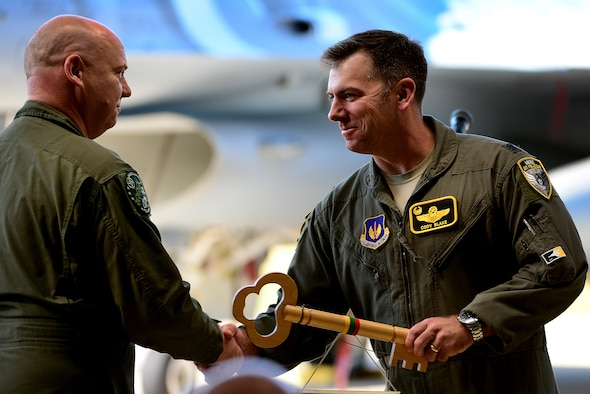 U.S. Air Force Lt. Col. Cody Blake, 493rd Expeditionary Fighter Squadron detachment commander, accepts the key to the Baltic Air Policing mission from Polish air force Lt. Col. Piotr Ostrouch during the official Baltic Air Policing hand-over, take-over ceremony at Šiauliai Air Base, Lithuania, Aug. 30, 2017. The 493rd EFS is slated to lead the Baltic Air Policing rotation through the end of the 2017 calendar year. (U.S. Air Force photo/ Tech. Sgt. Matthew Plew)