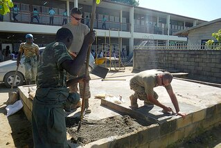 Soldiers from the South Dakota Army National Guard and members of Suriname Defense Force repair a concrete foundation while renovating portions of the O.S. Majosteeg 3 School in Paramaribo, Aug. 13-24
