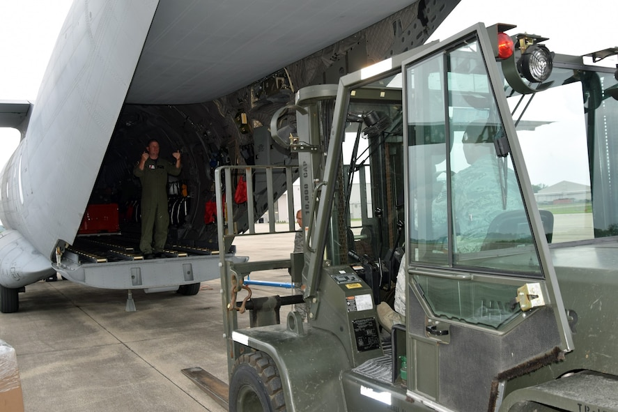 A U.S. Coast Guardsman assists members of the 127th Logistics Readiness Squadron, Small Air Terminal, in loading cargo onto a C-27 Spartan in advance of a deployment here on Tuesday. The 127th Wing, command unit of Selfridge Air National Guard Base, provided the expertise and equipment to U.S. Coast Guard Air Station Detroit, a longstanding active-duty unit based here since 1966.