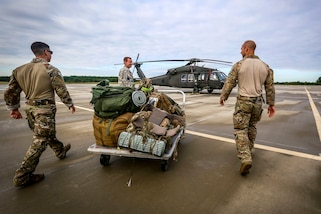 New Jersey Army and Air National Guardsmen take gear to a UH-60 Black Hawk helicopter.