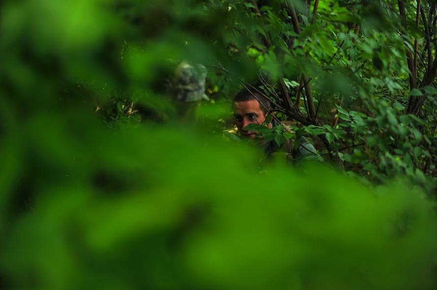 Airmen hiding behind trees