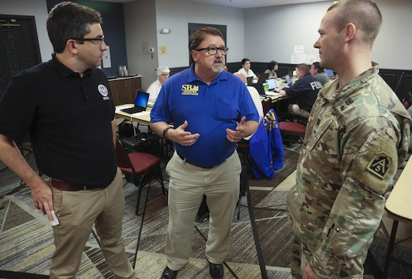 Daniel Green (left), an external affairs officer with Federal Emergency Management Agency's Region VIII Incident Management Assistance Team, Garth MacDonald (center), a public information officer with U.S. Small Business Administration, and Cpt. Anthony Hartman (right) , a U.S. Army North (Fifth Army) engineer augmentee to Region VI, discuss integration between local, state and federal assets supporting people affected by Tropical Storm Harvey Aug. 29 in Austin, Texas.
