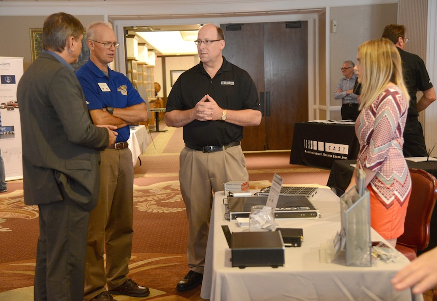 Tim Henke, center left, with the Air Force Association's Gerrity Chapter, speaks with Todd Prouty, Brian Rinehart and Abbie Obermiller, representatives for Crystal Group Inc., during the 13th Annual Technology Day at the Tinker Club Aug. 17.