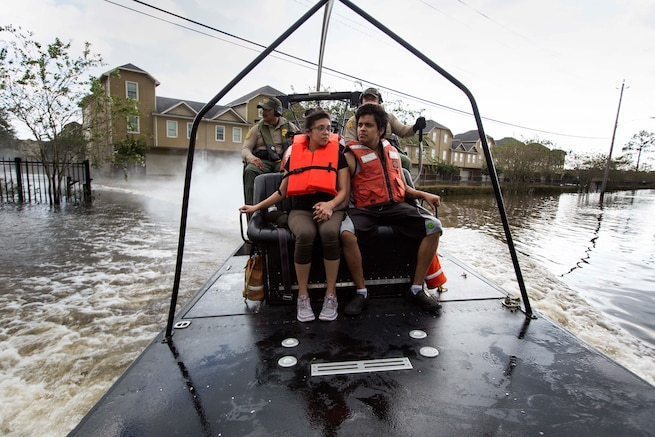 A Border Patrol agent drives an airboat carrying two boys wearing life vests.