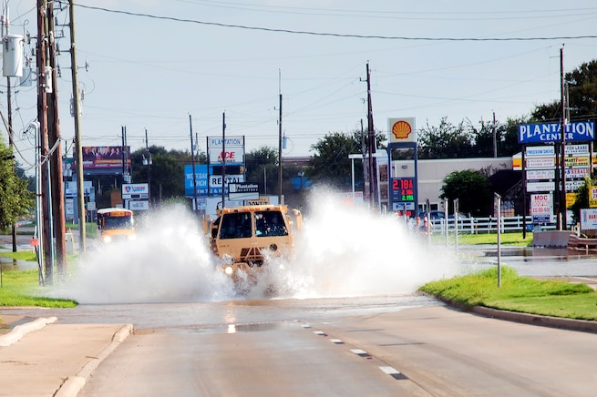 A military tactical vehicle creates a splash as it drives on a flooded street.