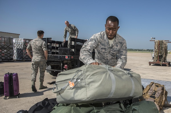 Airmen from the 59th Medical Wing readiness section load deployment bags for transport