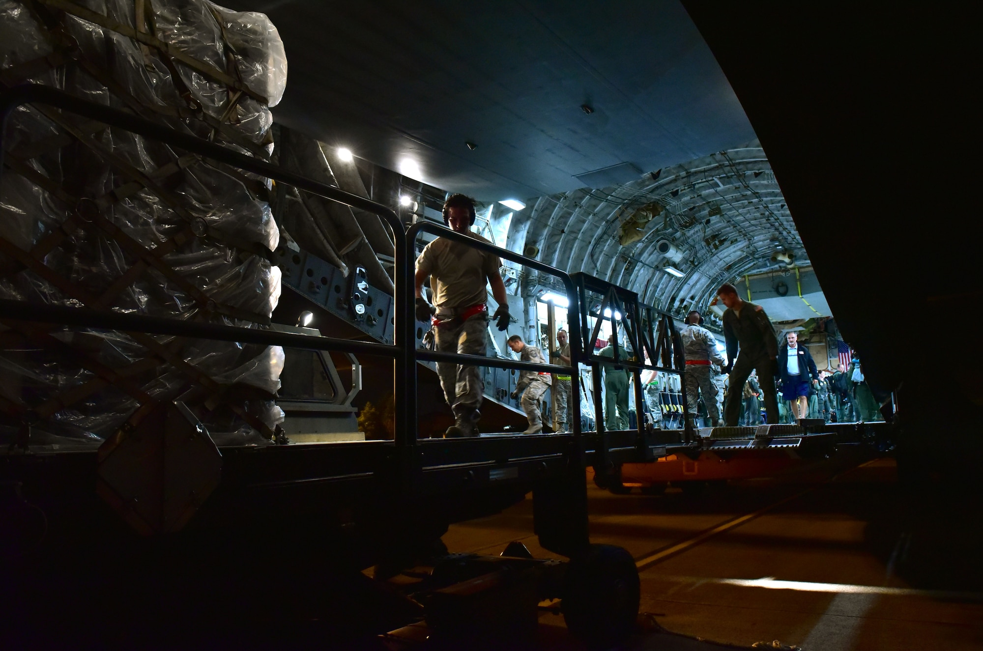 Cargo is loaded onto a C-17 by U.S. Airmen at night.