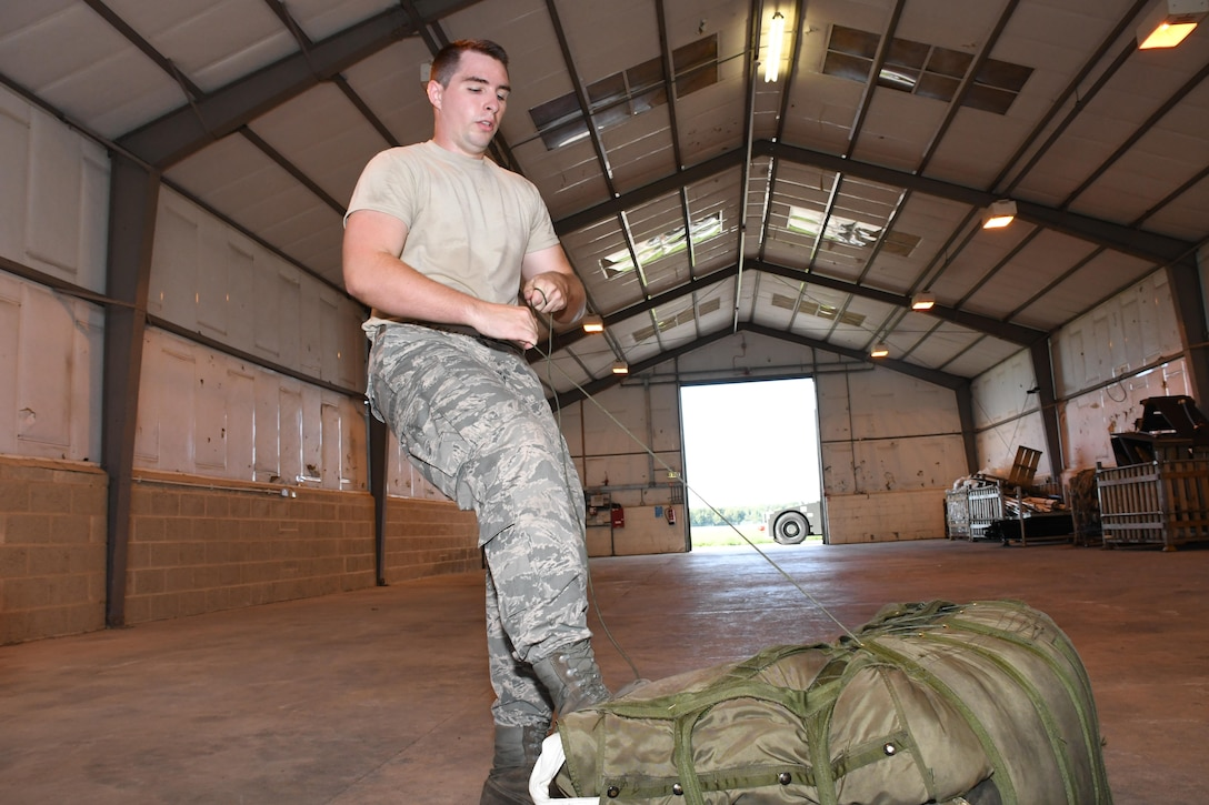 U.S. Air Force Senior Airman Jackson Stogsdill, a 307th Operations Support Squadron air flight equipment craftsman, ties up a bag containing drag chute for a B-52 Stratofortress at RAF Fairford, U.K., Aug. 28, 2017.