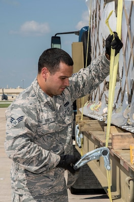 Senior Airman Vines, Taylor, 502nd Logistics Readiness Squadron, secures pallets loaded with medical supplies and equipment to a flatbed truck