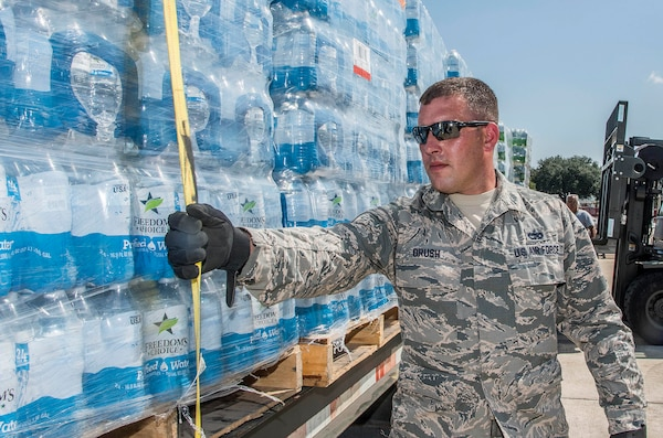Staff Sergeant James Brush, 502nd Logistics Readiness Squadron, prepares for transport over 30,000 water bottles
