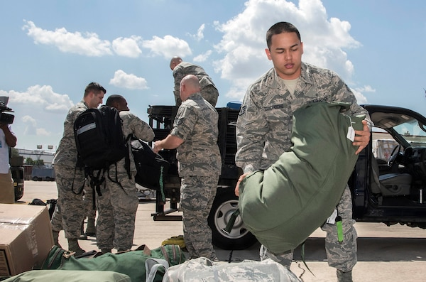 Airmen from the 59th Medical Wing prepare deployment bags for transport