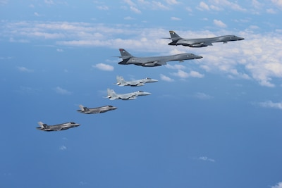 Marine Corps F-35B Lightning II stealth fighters assigned to the Marine Corps Air Station Iwakuni, Japan, fly alongside two Air Force B-1B Lancers assigned to the 37th Expeditionary Bomb Squadron, deployed from Ellsworth Air Force Base, South Dakota, over waters near Kyushu, Japan.