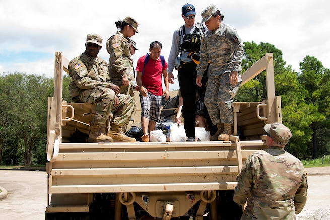 Guardsmen prepare to unload residents during water rescue operations in Texas.