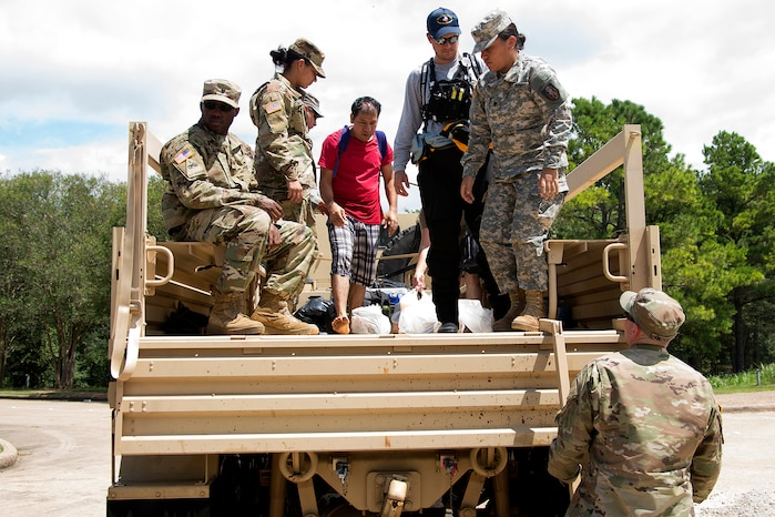 Texas Army National Guardsmen prepare to unload residents stranded by flooding caused by Harvey in Sugar Land, Texas
