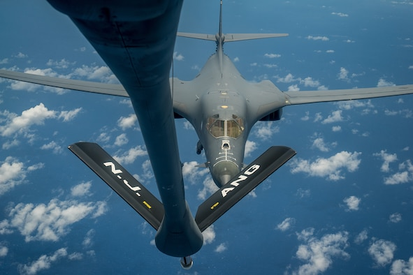 An aircraft refuels another aircraft in midair.