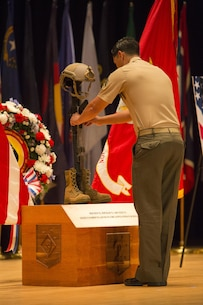 A critical skills operator with U.S. Marine Corps Forces, Special Operations Command, hangs the dog tags for one of seven fallen service members onto 2d Marine Raider Battalion's soldier's cross display at a celebration of life ceremony aboard Marine Corps Base Camp Lejeune, N.C., Aug. 31, 2017. Each person who spoke on behalf of one of the fallen service members, hung their respective dog tags onto the cross, which will be displayed at 2d MRB's headquarters building. The ceremony honored the seven MARSOC service members lost July 10 in a KC-130T Hercules transport aircraft crash, including Staff Sgts. Robert Cox and William Kundrat, Navy special amphibious reconnaissance corpsman, Petty Officer 1st Class Ryan Lohrey , and Sgts. Chad Jenson, Dietrich Schmieman, Joseph Murray, and Talon Leach. (U.S. Marine Corps photo by Sgt. Salvador R. Moreno, released)
