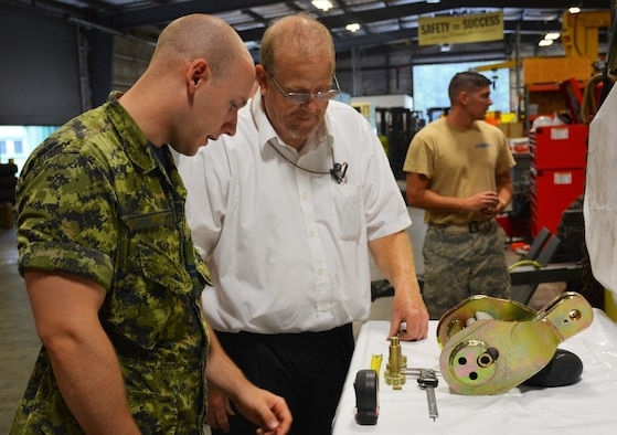 At left, Capt. Nicholas Sabine, Royal Canadian Air Force, 1 Canadian Air Division, A4 Construction Engineering and Dr. Craig Rutland, Air Force Civil Engineer Center, pavement subject matter expert and contact for Engineering Technical Letter, or ETL, 06-4 Expedient Trim Pad Anchoring Systems examine the components of the tape connector, a key part of the Aircraft Arresting System.