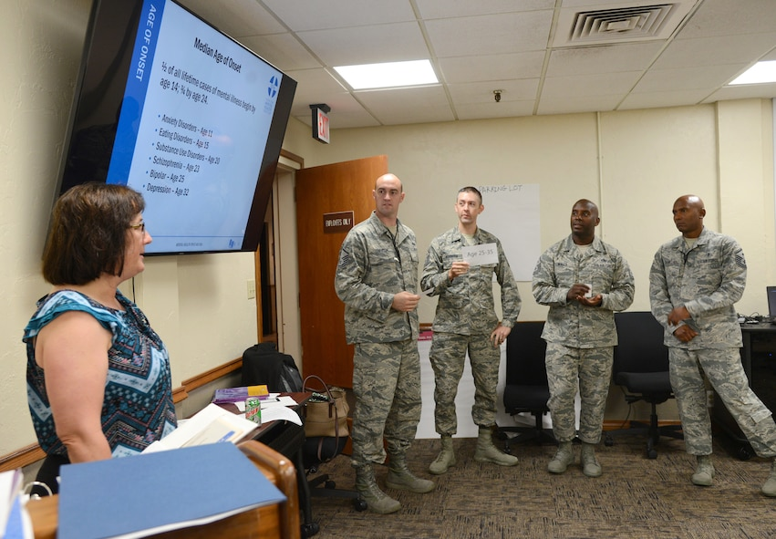 Community Support Coordinator Karen Blackwell leads an interactive activity during a Youth Mental Health First Aid Course Aug. 1 with Master Sgt. Nathan Thaxton, with the 373rd Training Squadron, and First Sgts. Tommy Stidham, with the 960th Airborne Air Control Squadron, David Wall, with the 963rd Airborne Air Control Squadron, and Enoch Daniels, with the 552nd Operations Support Squadron.