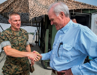 U.S. Marine Lt. Col. Foster Ferguson, the battalion commander with 1st Maintenance Battalion, Combat Logistics Regiment 15, 1st Marine Logistics Group, presents a 3-D printed coin made by the expeditionary manufacturer to Richard Spencer, the Secretary of the Navy, on Camp Pendleton, Calif., August 30, 2017. 1st Maintenance Battalion received their 3-D printer known as an expeditionary manufacturer in August, 2016. (U.S. Marine Corps photo by Lance Cpl. Adam Dublinske)