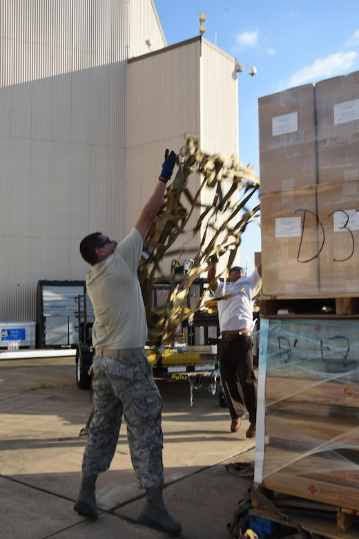 Air Force Tech. Sgt. Lucas Ortega, 73rd Aerial Port Squadron cargo supervisor, and Mr. Jose Guajardo, 301st Mission Support Group emergency management, toss webbing on a pallet to secure American Red Cross supplies before their transport August 29, 2017, at Naval Air Station Fort Worth Joint Reserve Base, Texas, in support of Hurricane Harvey relief efforts. There were 90,000 lbs. of supplies, included blankets and cots, sent as part of the Defense Support of Civil Authority. Department of Defense provides medium and heavy lift rotary wing assets, along with ground transportation, to move personnel, commodities and equipment within Texas. (U.S. Air Force photo by Ms. Julie Briden-Garcia)