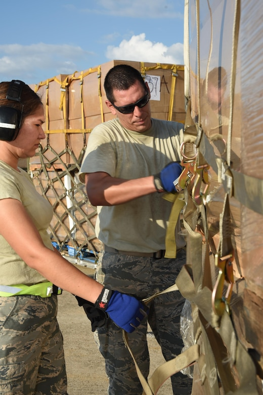 (left to right) Air Force Master Sgt. Viviana Molina, 73rd Aerial Port Squadron air transportation, and Tech. Sgt. Lucas Ortego, 73 APS cargo supervisor, secure webbing straps on 90,000 lbs. of American Red Cross supplies August 29, 2017, at Naval Air Station Fort Worth Joint Reserve Base, Texas, in support of Hurricane Harvey relief efforts. Supplies included blankets and cots and were transported as part of the Defense Support of Civil Authority. Department of Defense provides medium and heavy lift rotary wing assets, along with ground transportation, to move personnel, commodities and equipment within Texas. (U.S. Air Force photo by Ms. Julie Briden-Garcia)