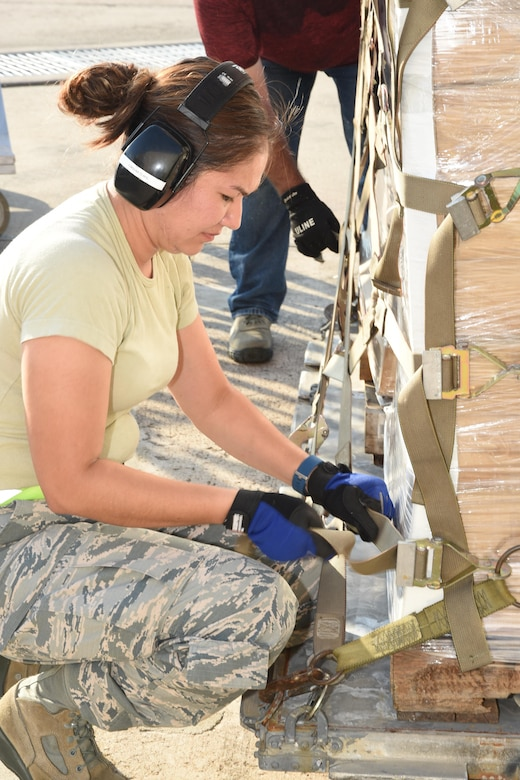 Air Force Master Sgt. Viviana Molina, 73rd Aerial Port Squadron air transportation, secures webbing straps on 90,000 lbs. of American Red Cross supplies August 29, 2017, at Naval Air Station Fort Worth Joint Reserve Base, Texas, in support of Hurricane Harvey relief efforts. Supplies included blankets and cots and were transported as part of the Defense Support of Civil Authority. Department of Defense provides medium and heavy lift rotary wing assets, along with ground transportation, to move personnel, commodities and equipment within Texas. (U.S. Air Force photo by Ms. Julie Briden-Garcia)