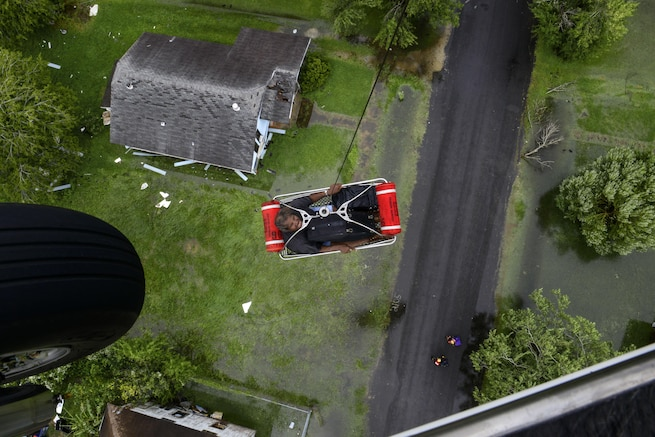 A helicopter hoists a resident lying in a basket up to a helicopter during a rescue.