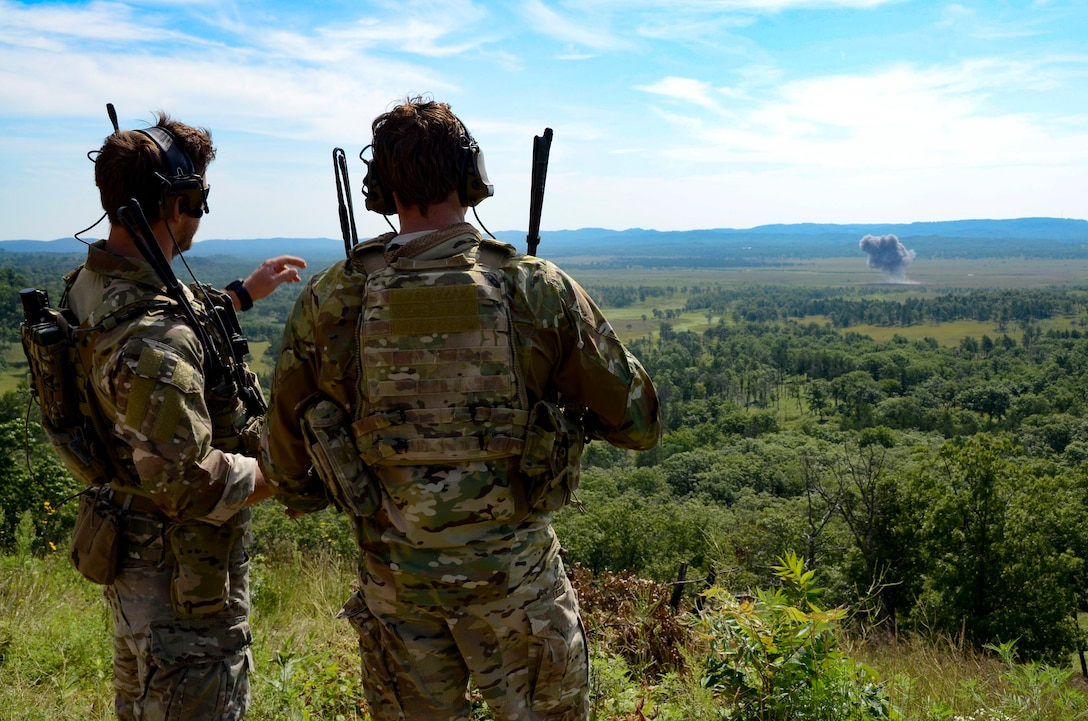 Tech. Sgt. Matt Lickel and Staff Sgt. Jackie Greathouse, U.S. Air Force Joint Terminal Attack Controllers (JTACs), watch as a Mark-82 high explosive bomb dropped by a 175th Fighter Squadron F-16 hits its target at the Fort McCoy, WI, live fire range Aug. 9, 2017.