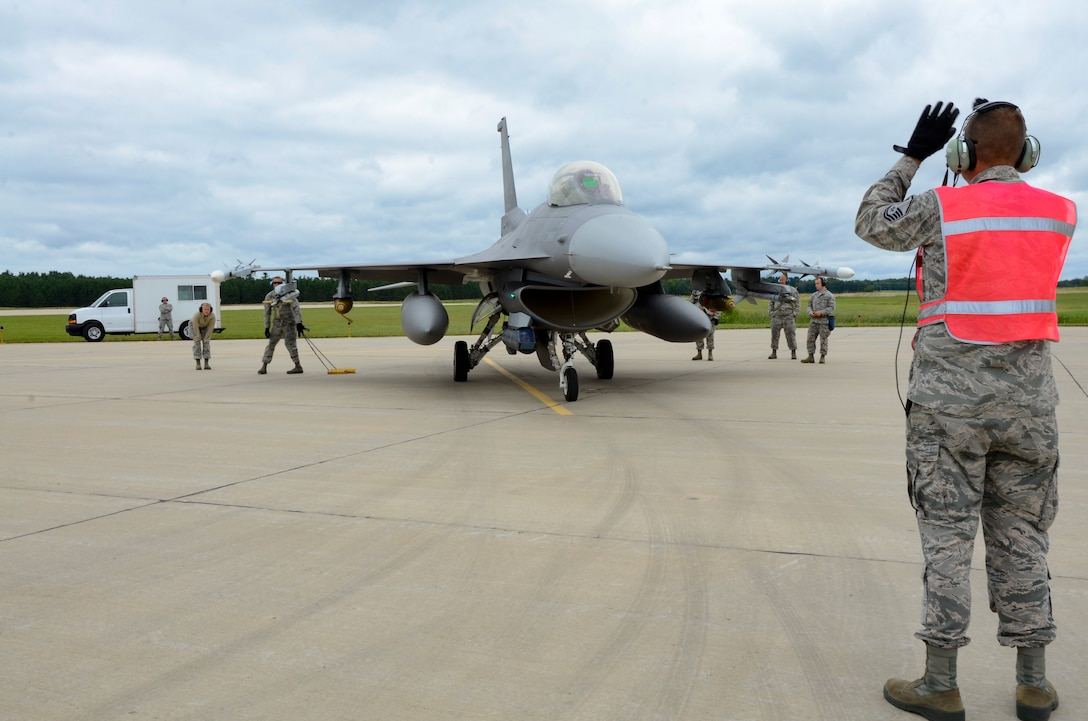 Master Sgt. Mike Rollag, 114th Fighter Wing crew chief, marshals a U.S. Air Force F-16 Fighting Falcon into last chance inspection at Volk Field, WI, Aug 11, 2017.