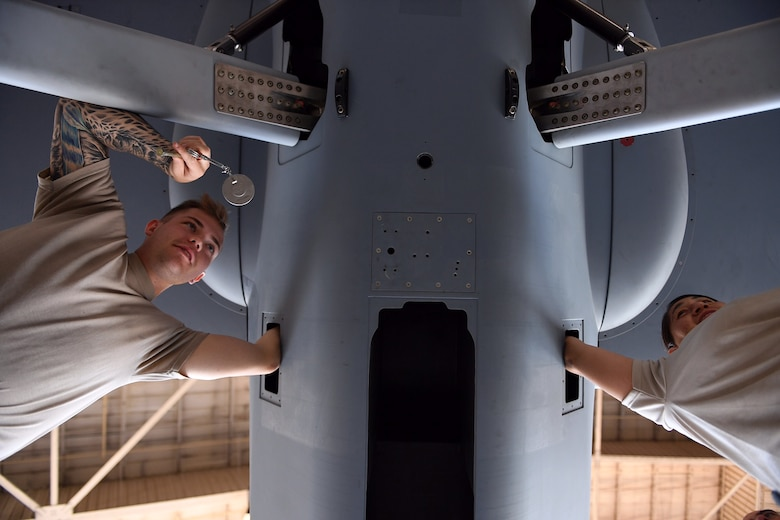 Airman 1st Class Conner and Staff Sgt. Nikki, both crew chiefs assigned to the 432nd Maintenance Group, work to assemble the MQ-9 Reaper model August 24, 2017, at Dover Air Force Base, Del., in preparation for the 2017 Thunder Over Dover Open House.