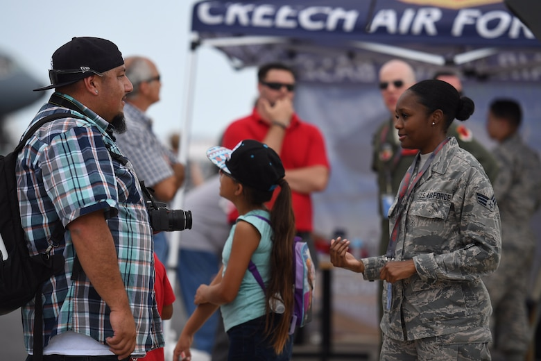 Senior Airman Tashiona, 432nd Wing intelligence analyst, explains her mission to a man attending the Thunder Over Dover Open House, Aug. 25, 2017, at Dover Air Force Base, Del.