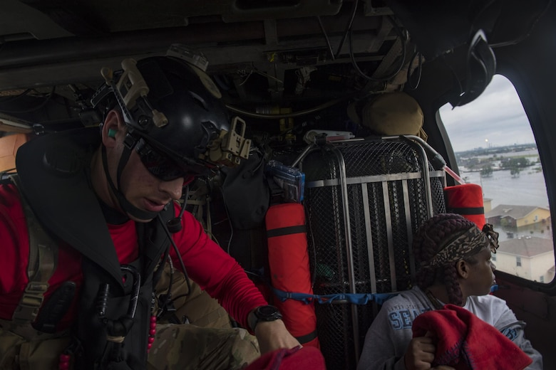 A pararescueman from the 38th Rescue Squadron reaches for more blankets for evacuees, Aug. 30, 2017, over the Houston, Texas area.