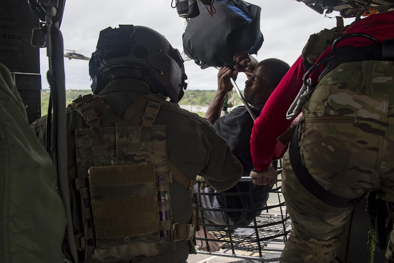 A special missions aviator from the 41st Rescue Squadron, and a pararescueman from the 38th Rescue Squadron, secures a basket carrying an evacuee, Aug. 30, 2017, over a residence in the Houston, Texas area.