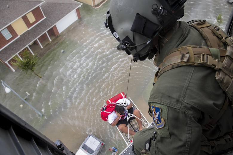 A special missions aviator from the 41st Rescue Squadron, watches as he raises an evacuee, Aug. 30, 2017, over a residence in the Houston, Texas area.