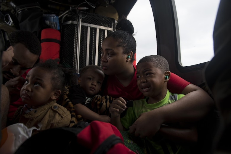 A family of evacuees wait for the rest of their family members onboard an HH-60G Pave Hawk, assigned to the 41st Rescue Squadron, Aug. 30, 2017, over a residence in the Houston, Texas area.